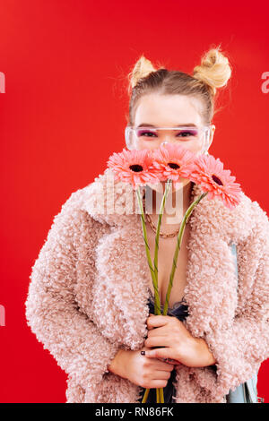Blonde woman with nice hairstyle smelling nice flowers - Stock Photo