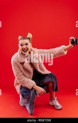 Cheerful positive woman laughing while making photo - Stock Photo