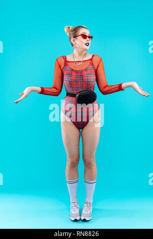 Fashionable slim model wearing red bodysuit and stylish necklace - Stock Photo