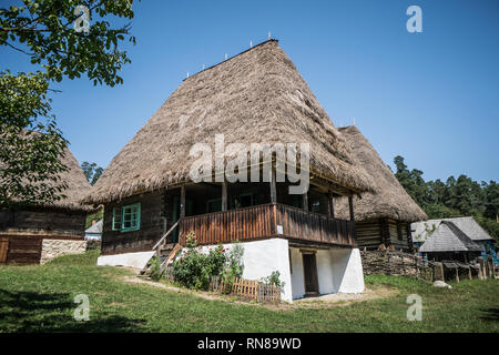 Traditional Romanian village home with grass hay roof in folk museum near Sibiu. - Stock Photo