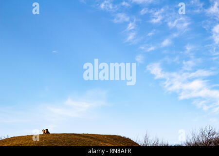 Young couple's heads behind hill with blue sky and cirro-stratus clouds - Stock Photo