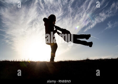 Silhouette of elder sister girl playing with younger child brother rotating spinning him round