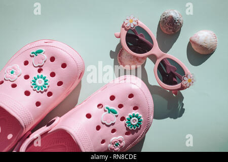 Travel vacation background concept with sunglasses and flip flops on pastel background. Top view with copy space. Flat lay. Clothes, shoes and - Stock Photo