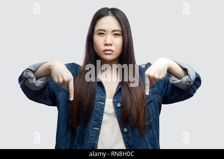 Here and right now. Portrait of serious bossy beautiful brunette asian young woman in casual blue denim jacket with makeup standing and pointing down. - Stock Photo