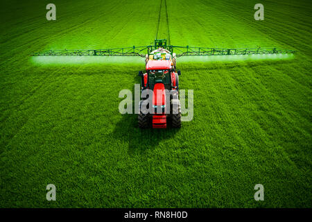 Фarming tractor plowing and spraying on green wheat field, aerial drone view - Stock Photo