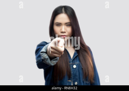 Hey you! Portrait of serious beautiful brunette asian young woman in casual blue denim jacket with makeup standing pointing and looking at camera. ind - Stock Photo