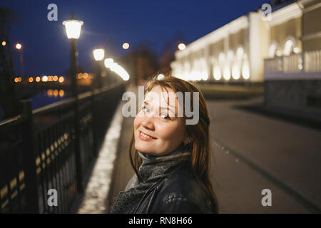 Portrait beautiful young woman in casual clothes walking on evening street. The city embankment of Vologda - Stock Photo