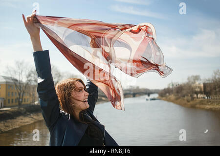 Cheerful girl holding a scarf, waving in the wind. Concept of spring, freedom, travel and windy weather. - Stock Photo