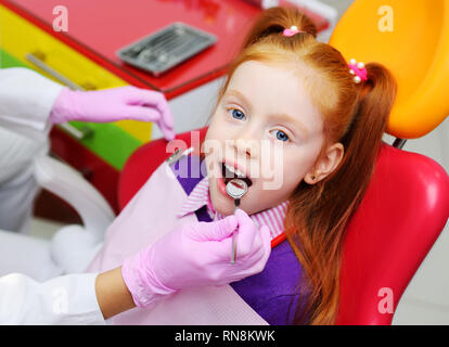 little girl smiling in red dental chair. The dentist examines the teeth of the child's patient.  - Stock Photo