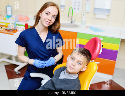 young woman dentist examines the teeth of a baby boy sitting in the dental chair. - Stock Photo