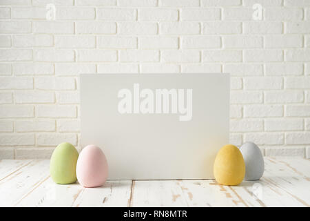 Easter composition with eggs, white board against white bricks wall