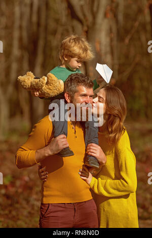 People play in autumn park having fun outdoor. Mother kiss father piggy backing cute small son. Treat people the way you want them to treat you - Stock Photo