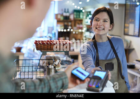 Male Customer Making Contactless Payment For Shopping Using Mobile Phone In Delicatessen - Stock Photo
