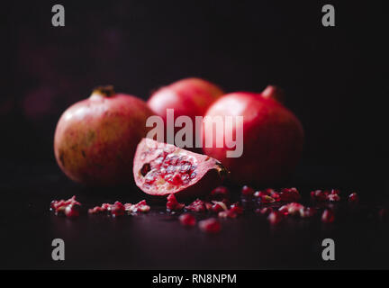 Still life of pomegranates in a Dutch Masters style, shot in natural light. The fruit has been sliced open to reveal the gem-like seeds within. - Stock Photo