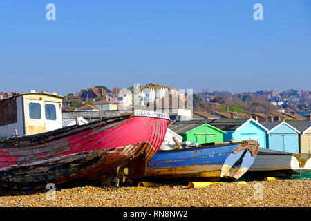 Old fishing boats and beach huts on the Bulverhythe beach, West St Leonards, East Sussex. UK