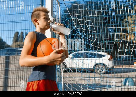 Teenager boy playing street basketball with ball on outdoor city basketball court drinking water. - Stock Photo