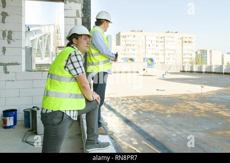 Male builders on the roof of construction site. Building, development, teamwork and people concept. - Stock Photo