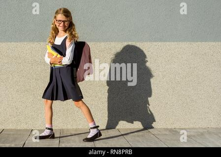 A schoolgirl of elementary school with notebooks in his hand. A girl with a backpack goes to school. Back to school - Stock Photo