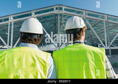 Male builders on roof of construction site,back view. Building, development, teamwork and people concept. - Stock Photo