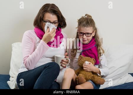 Sick mother and daughter. A woman with a runny nose, she sneezes, using a handkerchief, drinking hot tea, medicine. - Stock Photo