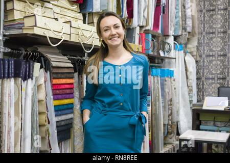 Portrait of happy mature woman owner in interior fabrics store, background fabric samples. Small business home textile shop - Stock Photo