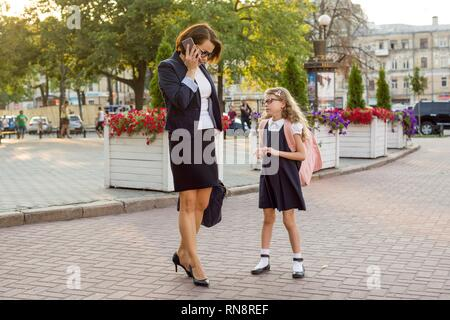 Mother businesswoman takes the child to school. - Stock Photo