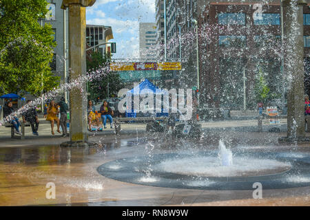 Tourists and locals enjoy a summer day at Riverfront Park in Spokane, Washington, as they sit around the Rotary Fountain and watch the water spray - Stock Photo