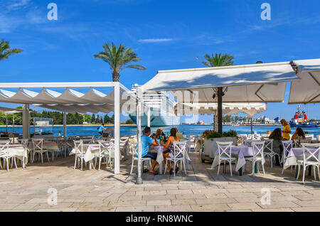 Tourists enjoy a waterfront afternoon meal on the Brindisi, Italy promenade as a large cruise ship prepares to dock on a summer day in Puglia. - Stock Photo