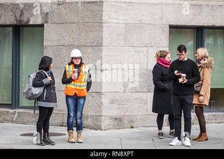 MONTREAL, CANADA - NOVEMBER 7, 2018:Young woman wearing safety PPE equipment, a helmet and an orange visibility vest discussing during her break with  - Stock Photo