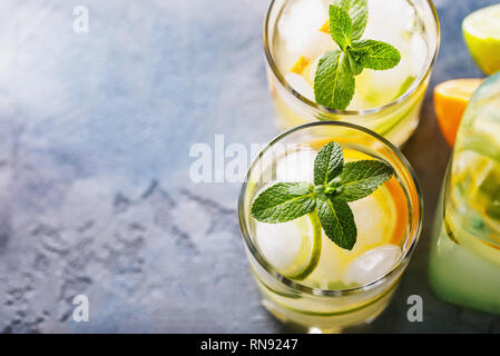 Water with a lemon and a lime in transparent glasses on a table with the copy space - Stock Photo