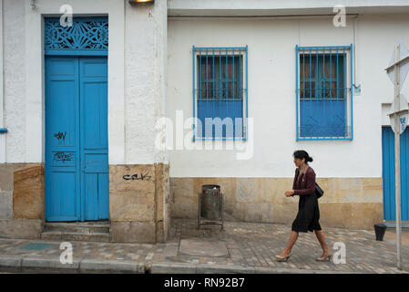 Local woman walking past colonial building with bright blue windows. La Candelaria, the historic district of Bogota, Colombia. Sep 2018 - Stock Photo
