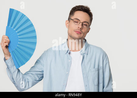 Overheated young man sweating waving fan isolated on background - Stock Photo
