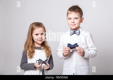 Cute boy and girl in fashionable clothes with bow tie posing on grey background. Portrait of fashionable children. The concept of children's fashion a - Stock Photo