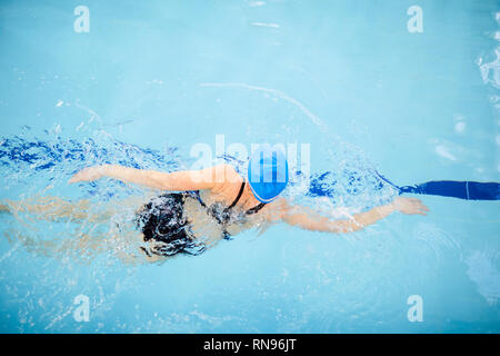 Unrecognizable Woman Swimming in Pool - Stock Photo