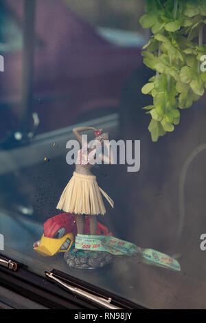 Hula dancer doll on dashboard of car - Stock Photo