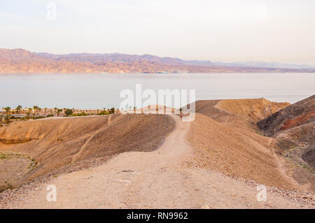 Sandy curved walking pathway from the desert mountains down to the Red Sea bay shore and beaches in Eilat, Israel with Jordan coast on the background - Stock Photo