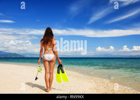 Young woman in bikini standing on a beach with mask, snorkel and fins - Stock Photo