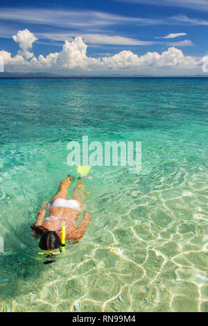 Young woman snorkeling in clear shallow water near tropical island - Stock Photo
