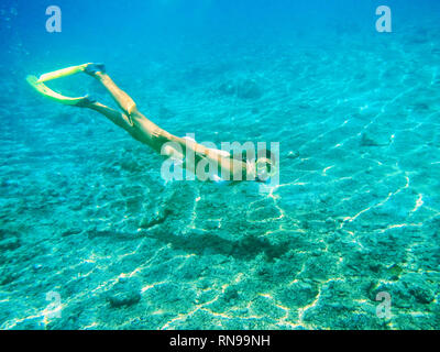 Young woman diving with snorkel in clear water near tropical island - Stock Photo