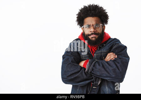 Waist-up shot of intense and bothered gloomy angry african american bearded man in glasses looking with judgement and disapproval frowning and sulking - Stock Photo