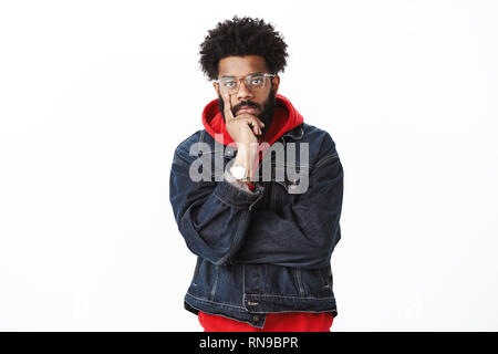 Serious-looking throughtful good-looking african-american hip-hop dancer with beard in glasses and denim jacket over hoodie touchign face with finger - Stock Photo