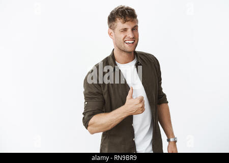 Hey you doing awesome. Portrait of friendly enthusiastic handsome fair-haired bearded guy winking at you and showing thumbs up in like and approval - Stock Photo