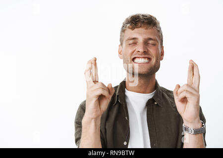Excited and happy attractive fair-haired guy with bristle close eyes thrilled and smiling delighted as waiting for dream finally came true, cross - Stock Photo