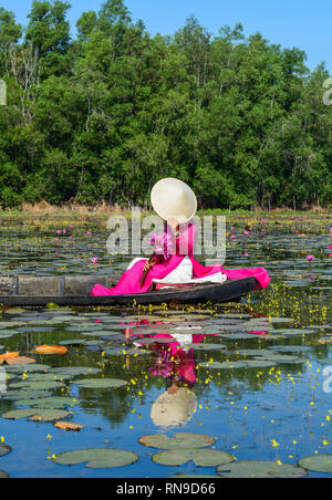 Asian woman in traditional dress (Ao Dai) sitting on the wooden boat in waterlily pond. - Stock Photo
