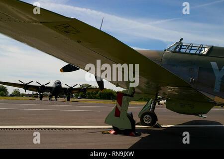Royal Air Force Battle of Britain Memorial Flight Hawker Hurricane fighter plane framing Avro Lancaster bomber. Second World War planes - Stock Photo