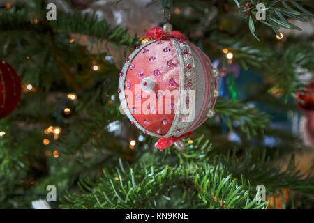 Old fashioned, hand made fabric-covered traditional Xmas bauble decoration with vintage lace, made by Tobias and the Angel, on a Christmas tree - Stock Photo