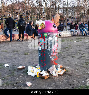 Mauer Park,Berlin, Germany, 17th February 2019. Overflowing trash cans -  a sign of a warm weekend. Berliners are enjoying a glorious Spring-like weekend in the middle of February - normally the second coldest month of the year. People relax in Mauerpark and enjoy the blue skies, sunshine and unseasonal warmer weather. Credit: Eden Breitz/Alamy Live News - Stock Photo