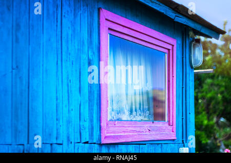 Minimalist Design Concept: Vivid Purple Window Frame, a Light on Blue Wall of Wooden Planks. Mountains Reflection in Glass, White Curtain. Roof Eaves. - Stock Photo