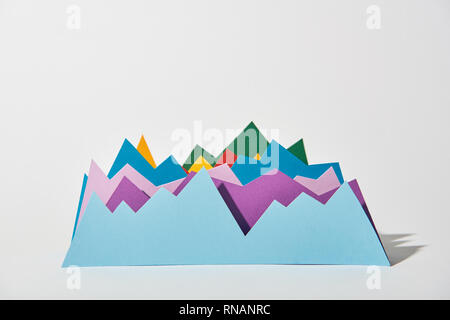 blue, purple, green, red and yellow paper graphs on white background - Stock Photo