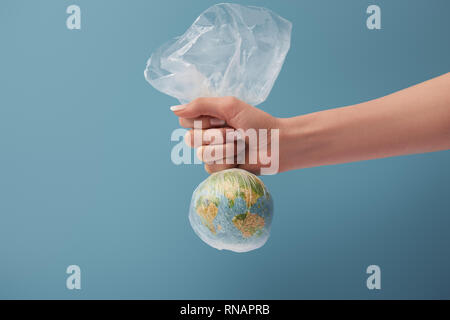 cropped view of woman holding globe in plastic clear bag on blue background - Stock Photo